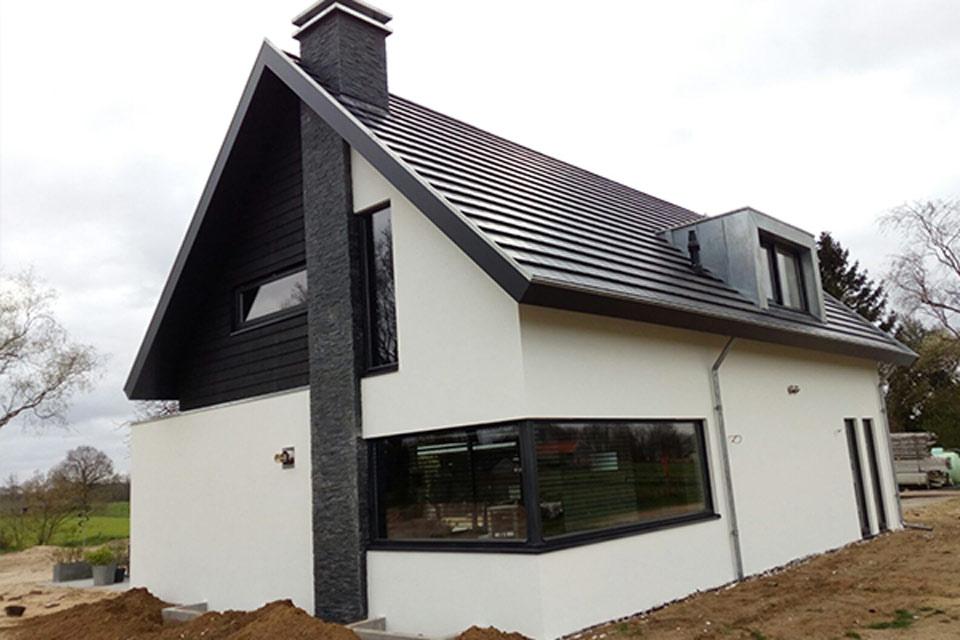 wit gestucte woning met zwart hout